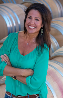Jennifer Smith in front of wine barrels