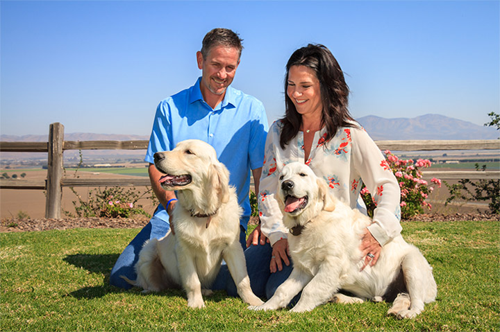 Jen and Jason with 2 white dogs sitting on a green lawn.