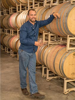 Justin in the cellar leaning against wine barrels.